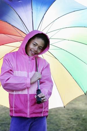 Girl holding a colourful umbrella Stock Photo - 10862125