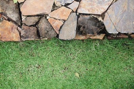 Stone wall and fresh green grass photo