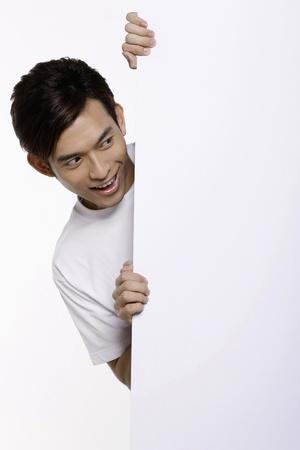 Man peeking from behind white placard