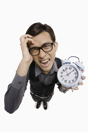 high angle shot: Businessman screaming while holding alarm clock Stock Photo