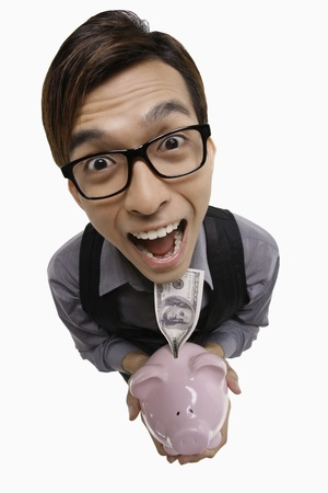 Businessman looking excited while holding piggy bank with money photo