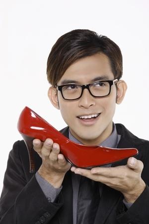 Businessman thinking while holding red stiletto shoe Stock Photo - 10862135