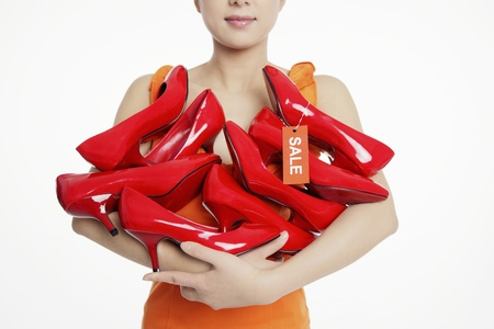Woman with an armful of shoes