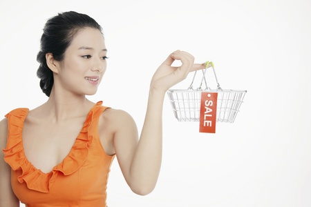 Woman holding shopping basket with sale label photo