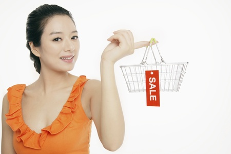 Woman holding shopping basket with sale label Stock Photo - 12514697