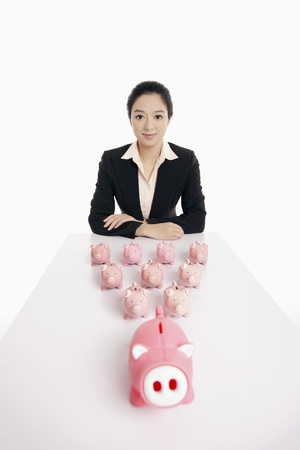 Businesswoman with piggy banks on the table photo