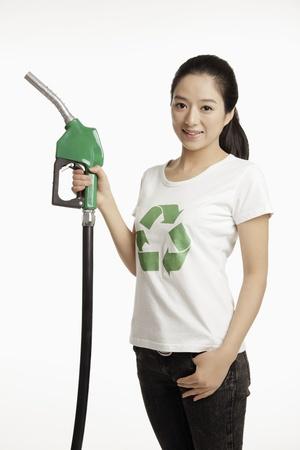 fuel pump: Woman holding a petrol pump
