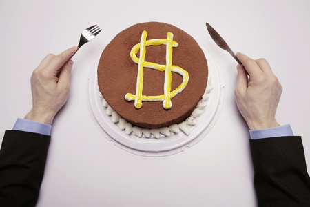 Businessman preparing to eat cake with dollar sign photo