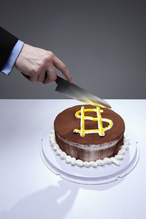 Businessman cutting cake with dollar sign photo