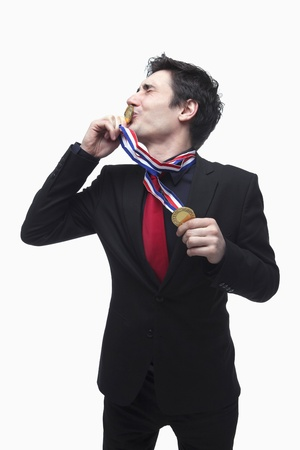 Businessman kissing gold medal photo