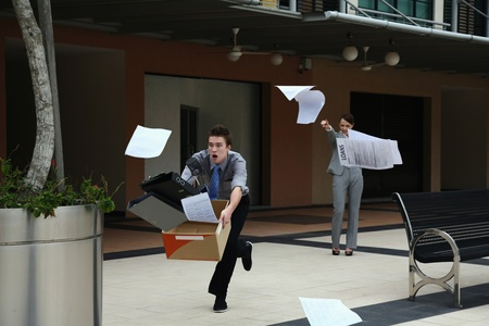 Businesswoman throwing papers, businessman catching them photo