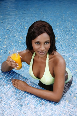 Woman with a glass of orange juice leaning on pool edge photo