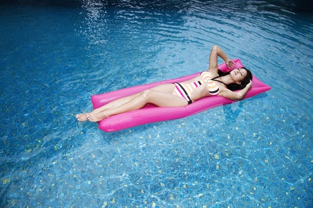 Woman floating on lilo photo