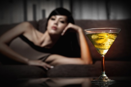 A glass of martini, woman lying on the couch in the background photo