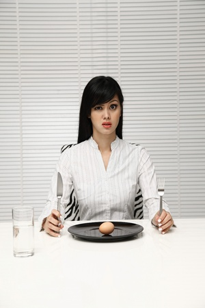 Woman sitting at the table holding table knife and fork photo