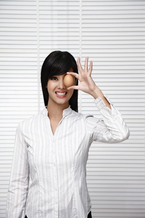 Woman covering eye with egg photo