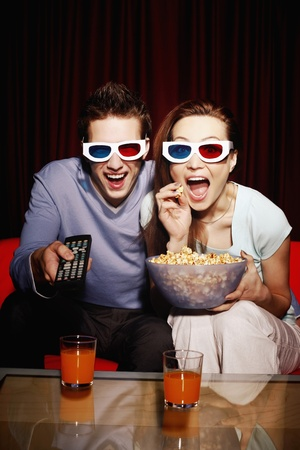 popcorn bowls: Man and woman watching 3D movie Stock Photo