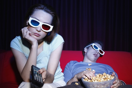 Woman watching 3-D movie, man falling asleep photo