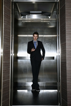people in elevator: Businessman text messaging in the elevator Stock Photo