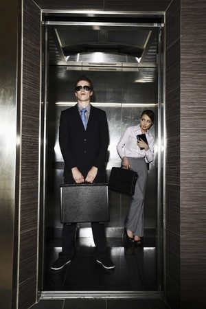 people in elevator: Businesswoman looking at businessman with sunglasses Stock Photo