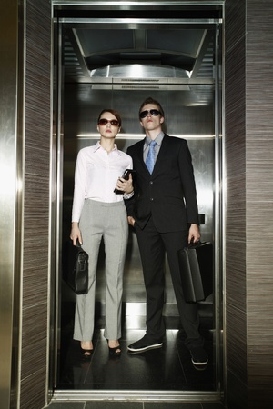 people in elevator: Business people with sunglasses standing in elevator