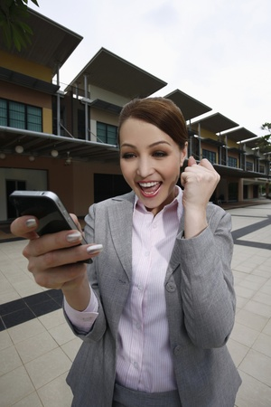 jubilating: Businesswoman cheering while reading text messages