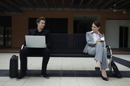 Businessman using laptop, businesswoman writing on organizer photo