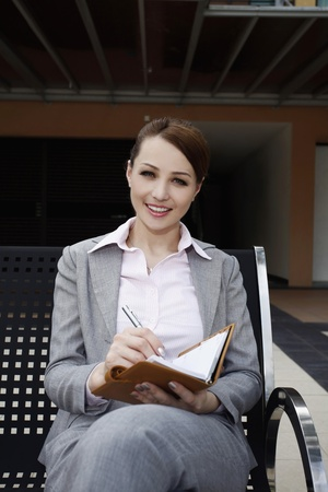 Businesswoman writing on organizer photo