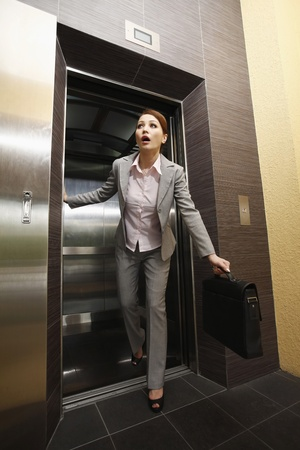 Businesswoman rushing out of the elevator Banque d'images
