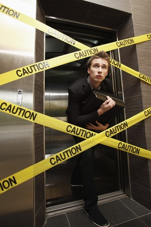 Businessman sneaking out of a cordon taped elevator Banque d'images