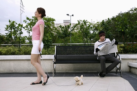 Woman walking her dog, man reading newspaper on the bench photo