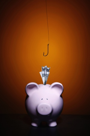 Money in piggy bank slot, fishing hook hanging above Stock Photo - 13147155