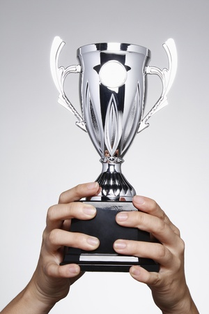 winning idea: Hand lifting up a silver trophy Stock Photo