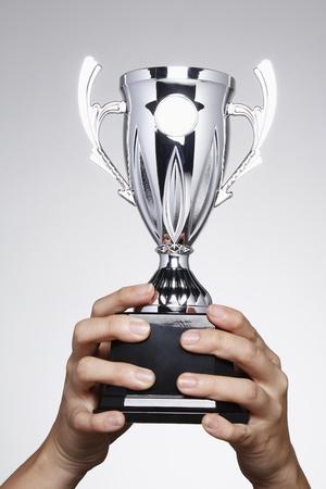 levantar peso: Mano levantando un trofeo de plata