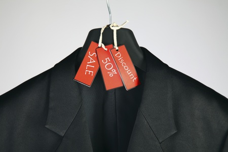 coathanger: Suit on coathanger with sale tag Stock Photo