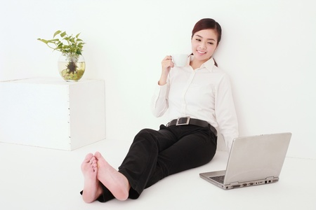 Businesswoman drinking coffee while using laptop Stock Photo - 13341567
