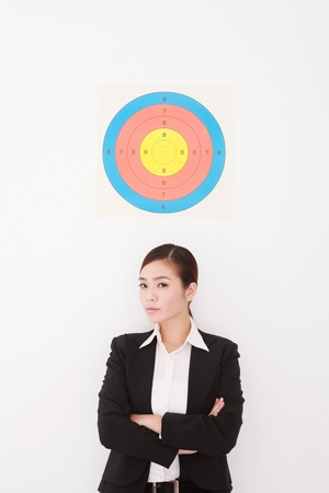 folding arms: Businesswoman with target above her head, folding her arms