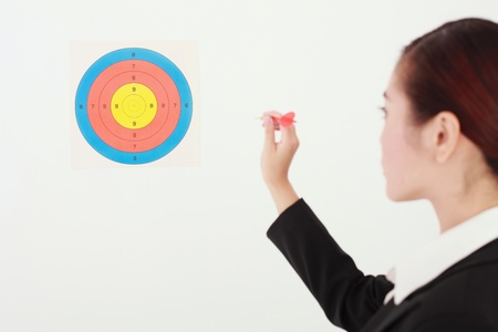 Businesswoman throwing dart at target photo
