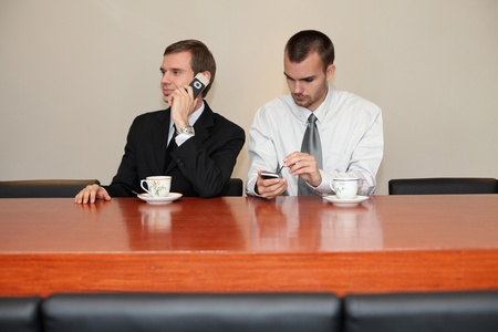 Businessman talking on the phone while his colleague is text messaging on the phone Stock Photo - 13441088