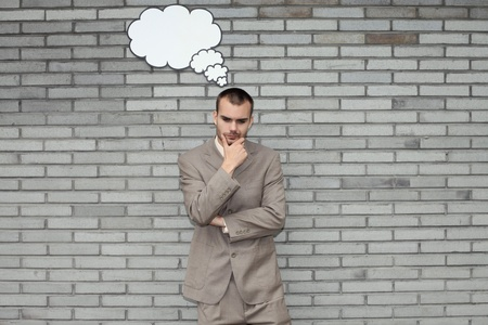 Businessman with thought bubble with hand on chin Stock Photo - 13355304
