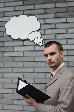 Businessman with thought bubble while writing in organizer Stock Photo - 13355183