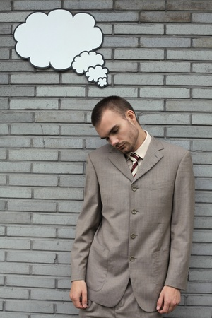 Businessman with eyes closed and a thought bubble above his head photo