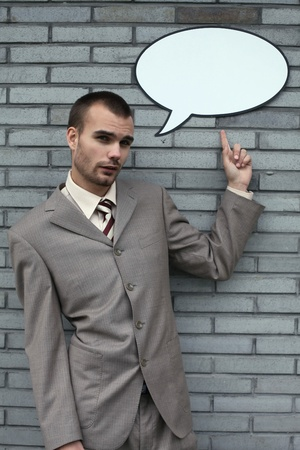 Businessman pointing at speech bubble photo
