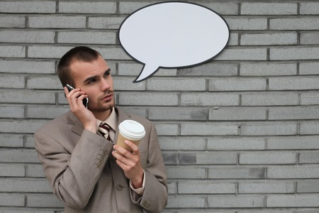 Businessman with speech bubble talking on the phone and holding a cup of coffee photo