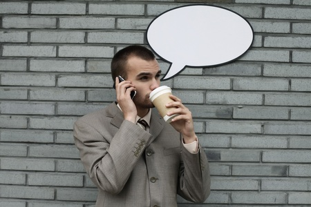 Businessman with speech bubble talking on the phone and drinking coffee Stock Photo - 13355292