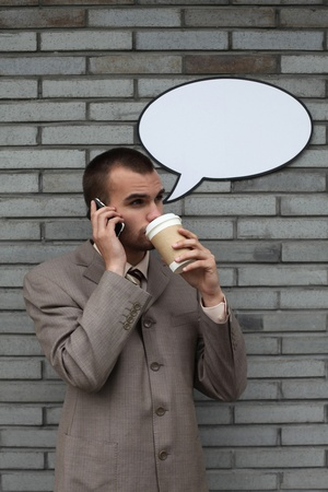 Businessman with speech bubble talking on the phone and drinking coffee photo