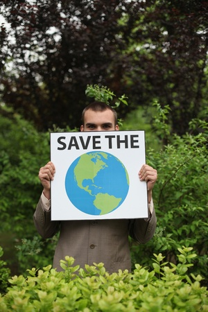 environmental awareness: Businessman holding a card saying