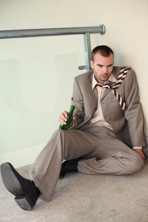 Drunk businessman sitting on the floor holding beer bottle photo