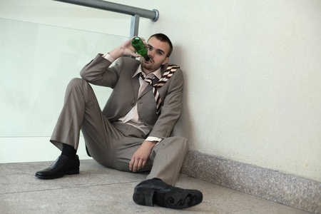 Businessman sitting on the floor drinking beer Stock Photo - 13355301