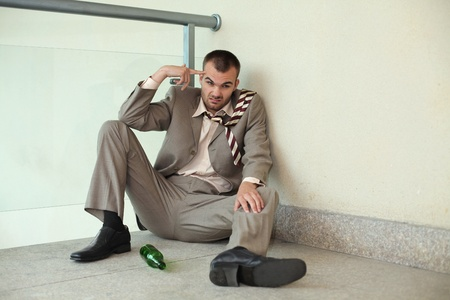 Drunk businessman sitting on the floor pointing at his head